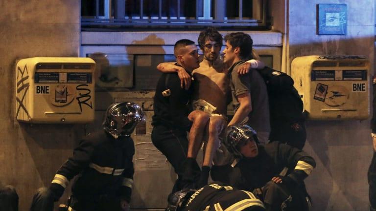 French fire brigade members aid an injured individual near the Bataclan following fatal shootings in Paris.