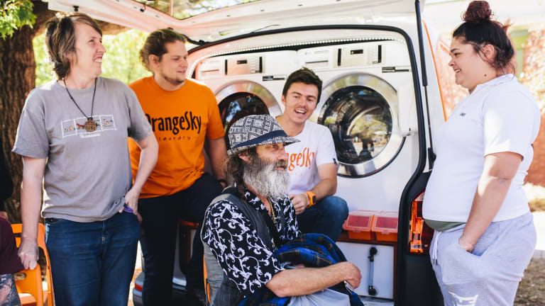 """Queanbeyan local Haralg Haralg """"Harry'' (seated) gets his clothes washed and dried by the Orange Sky Laundry van in Queanbeyan on Wednesday with (l-r) St Benedict's Community Centre manager Elaine Lollback, Orange Sky Laundry founders Lucas Patchett and Nic Marchesi, and centre user Sylvia Brumm."""