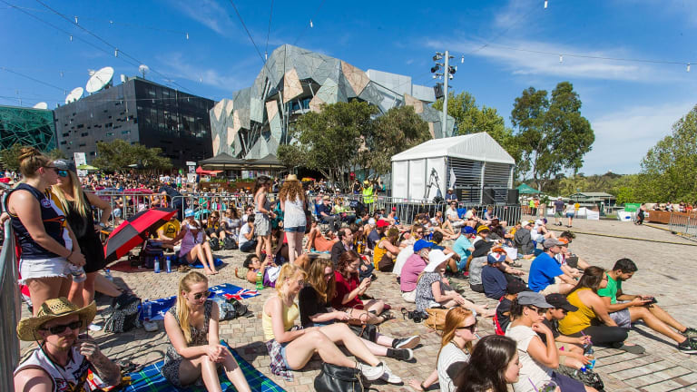 Fans settle in at Federation Square to watch the grand final in the sun.