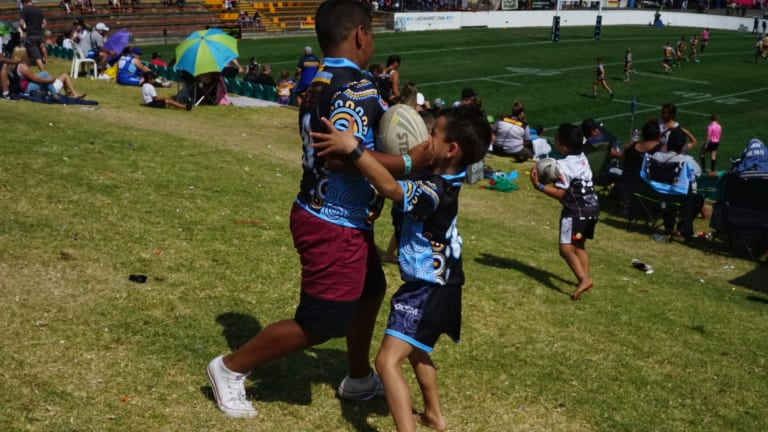 Mismatch: Kids play footy on the grass hill at Leichhardt Oval.