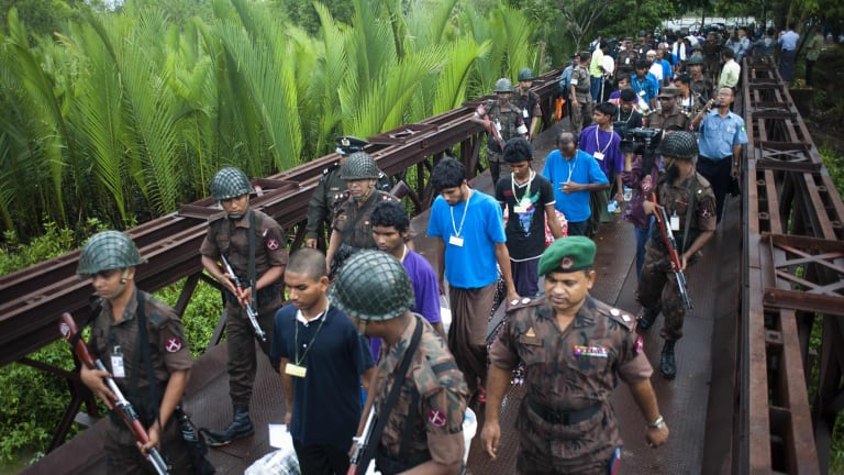 Migrants who were found at sea on a boat are repatriated across the Myanmar-Bangladesh border on Monday.