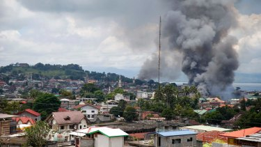 Smoke rises from houses following airstrikes by Philippine Air Force bombers as government forces battle to retake control of Marawi.