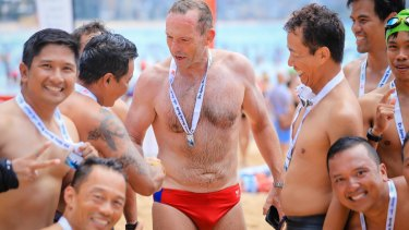 Former PM Tony Abbott is congratulated after finishing the 2km swim in the Sydney Morning Herald Cole Classic at Manly in February.
