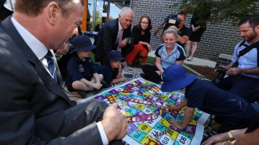 """Who's winning?"": children at the centre play Snakes and Ladders."