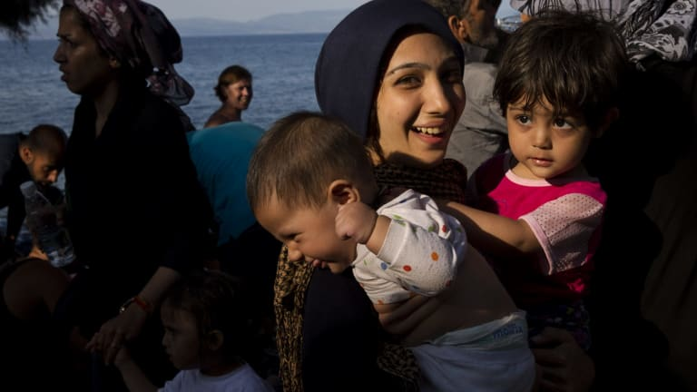 A migrant holds two children as they arrived on a dinghy after crossing from Turkey to Lesbos island, Greece, on Tuesday.