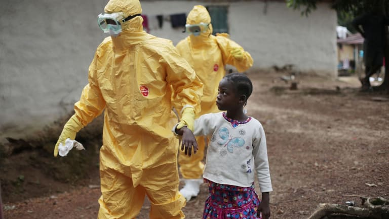 A young girl is taken to an ambulance after showing symptoms of Ebola during the 2014 outbreak in Liberia.