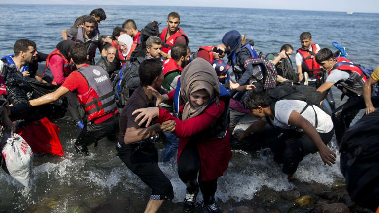 Migrants and refugees arrive on a dinghy after crossing from Turkey to Lesbos Island, Greece. The island of some 100,000 residents has been transformed by the sudden new population of some 20,000 refugees and migrants, mostly from Syria, Iraq and Afghanistan.
