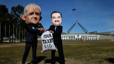 Protestors wearing suits resembling Prime Minister Malcolm Turnbull and Adani chief, Gautam Adani, take part in a protest in Canberra on Thursday.