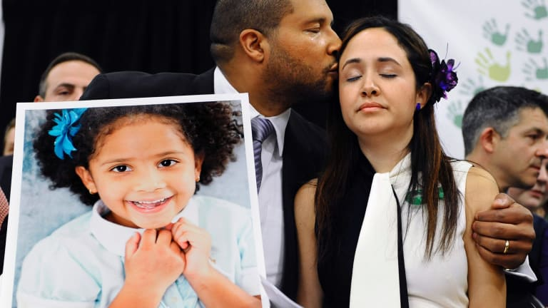 Jimmy Greene kisses his wife Nelba Marquez-Greene while holding a portrait of their slain daughter Ana Marquez-Greene.