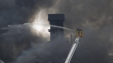 Firefighters on a ladder spray water to put out the fire at a packaging factory in Tongi industy area outside Dhaka.