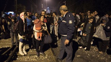 A Greek police officer gives orders to Syrians as they wait to cross the border from Greece to Macedonia at the weekend.