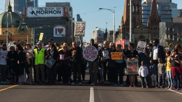The vigil for Faysal Ishak Ahmed takes to the street as protesters block traffic both ways on St Kilda Road.