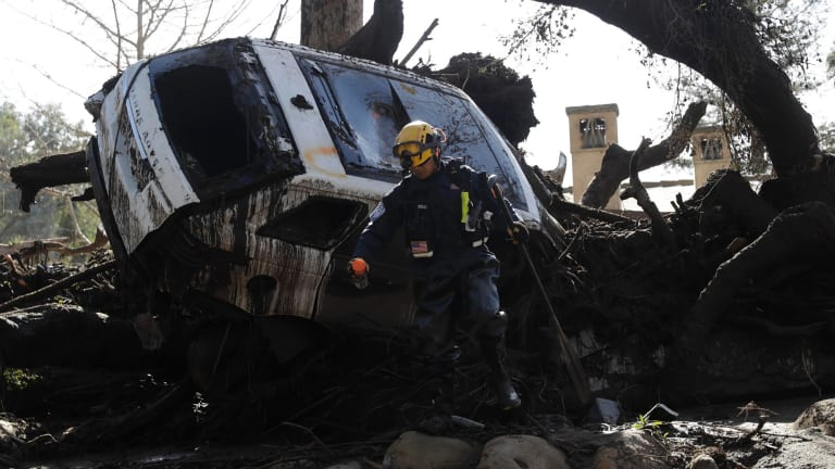 Crews look for survivors near a car trapped under debris in Montecito.