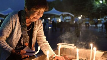 A woman lights a candle as she prays for the atomic bomb victims in front of the cenotaph at the Hiroshima Peace Memorial Park on Saturday August 6.