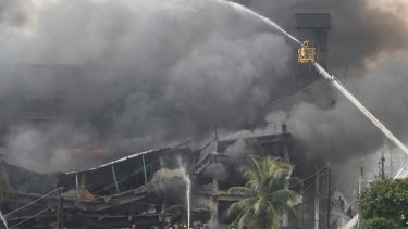 Firefighters on a ladder work to put out the fire at a packaging factory in Tongi industry area outside Dhaka.