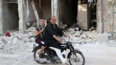 A man with a leg cast rides a motorcycle though a bomb-damaged area in Old Aleppo on Thursday.