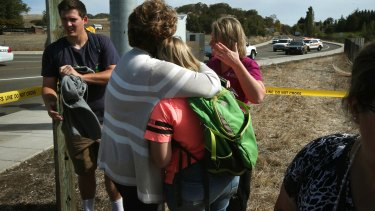 Grim toll: People console each other on a road leading to the Umpqua Community College campus in Roseburg on Thursday.
