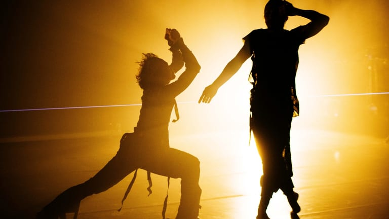 The lighting creates its own form of communication around the dancers.
