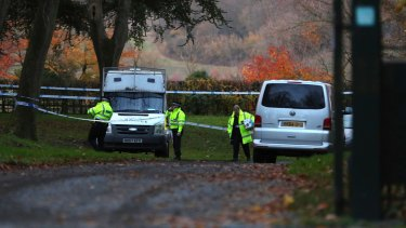 Police patrol the area near the scene of a mid-air collision between a helicopter and an aircraft, in Buckinghamshire.