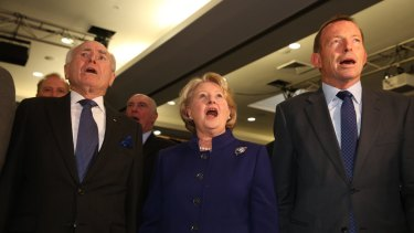 John Howard, Janette Howard and Tony Abbott sing the national anthem.
