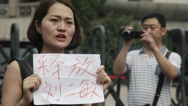 "A man films Li Wenzu, left, wife of imprisoned lawyer Wang Quanzhang, holding a paper that reads ""Release Liu Ermin""  outside the Tianjin court on Monday.  Liu Ermin is a wife of one of the activists, who was arrested on Sunday, July 31."