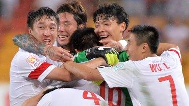 Super sub: Sun Ke is mobbed by teammates after scoring the winner for China against Uzbekistan in Brisbane.