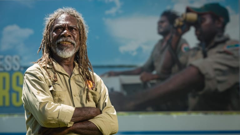 Wardekken ranger and fire management leader Dean Yilbarbuk with the billboard outside Darwin Airport highlighting the importance of the Indigenous Ranger movement.