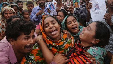 Relatives of a Bangladeshi garment worker killed in the Rana Plaza factory collapse mourn as they collect his body.