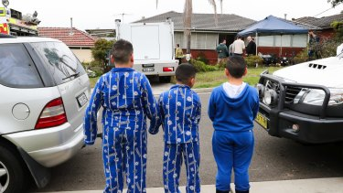 Children watch as police search a house on Pollock Street, Georges Hall.
