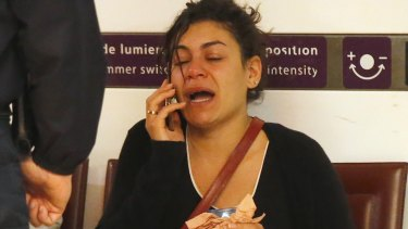 A relative of the victims reacts as she makes a phone call at Charles de Gaulle Airport outside Paris.