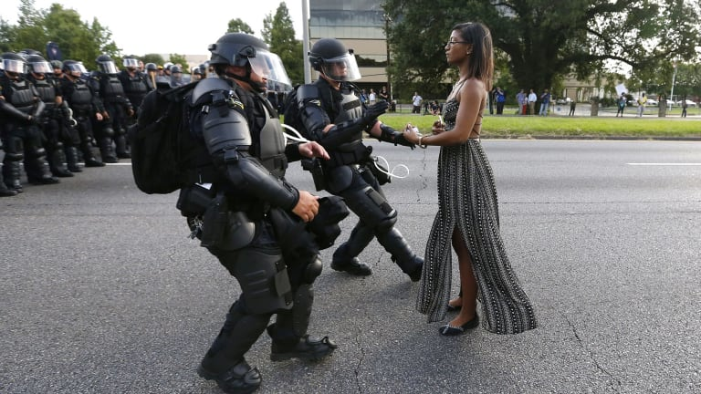 Police officers in riot gear face a woman in a dress during a Black Lives Matter protest in Baton Rouge.