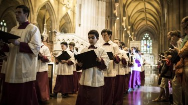 Choristers sing in file at St Mary's Cathedral, Sydney for the Christmas Day Mass.