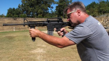 "Shooting instructor Frankie McRae aims an AR-15 rifle fitted with a ""bump stock"" at his 37 PSR Gun Club in North Carolina."
