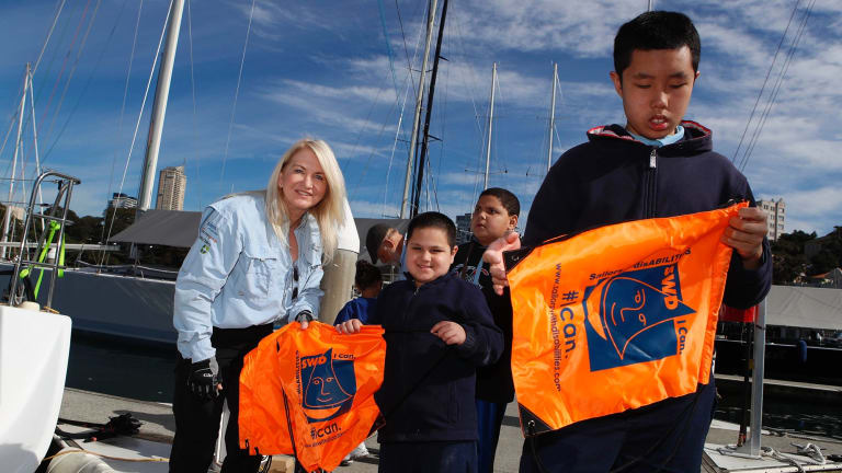 Members of the group Sailors with DisABILITIES Khan and Hao Nguyen from Wairoa School receive presents from Ann Flynn in Sydney.