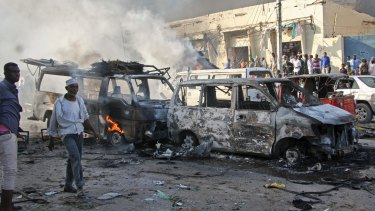 Somalis walk past the wreckage of vehicles at the scene of a blast in Mogadishu.