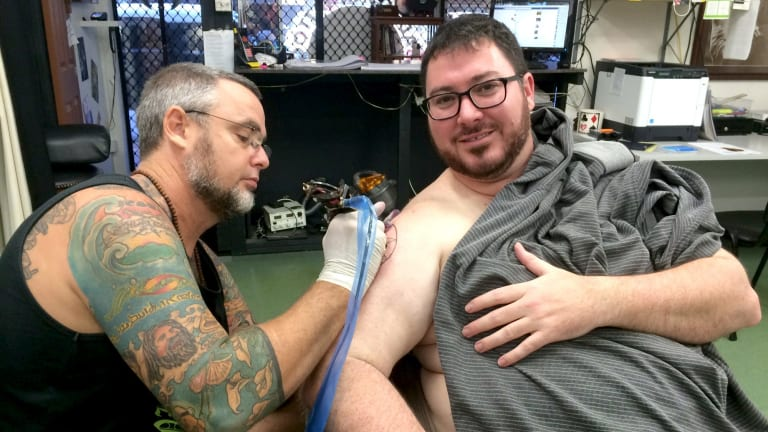 George Christensen is given his Coptic Madonna tattoo by Dave Phare from Mad Monk Tattoos in Mackay.