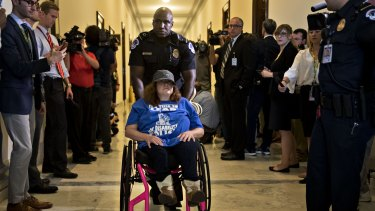 A demonstrator in a wheelchair protests cuts to Medicaid.