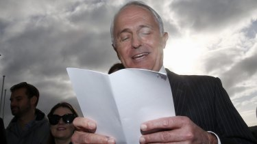 Prime Minister Malcolm Turnbull reads from a list of ALP spending pledges on Tuesday.