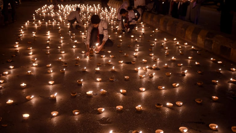 Pakistani students light lamps for the victims of an attack by Taliban gunmen.