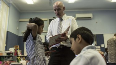 Westmead principal Adrian Mort helps year 2 students with their spelling.