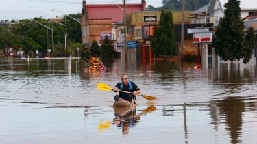 A man paddles a kayak down a street in Lismore.
