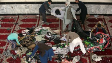 Afghan men collect  belongings inside a damaged mosque in Kabul on Saturday.