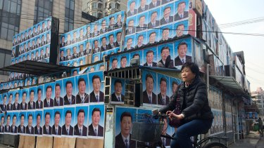 A building covered in portraits of Xi Jinping in Shanghai.