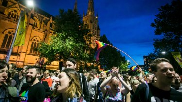 Marriage equality advocates celebrating the ''yes'' vote mark past St Mary's Cathedral in Sydney on Wednesday.