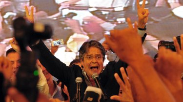 Guillermo Lasso flashes victory signs as he awaits final election results in Guayaquil, Ecuador, on Sunday.
