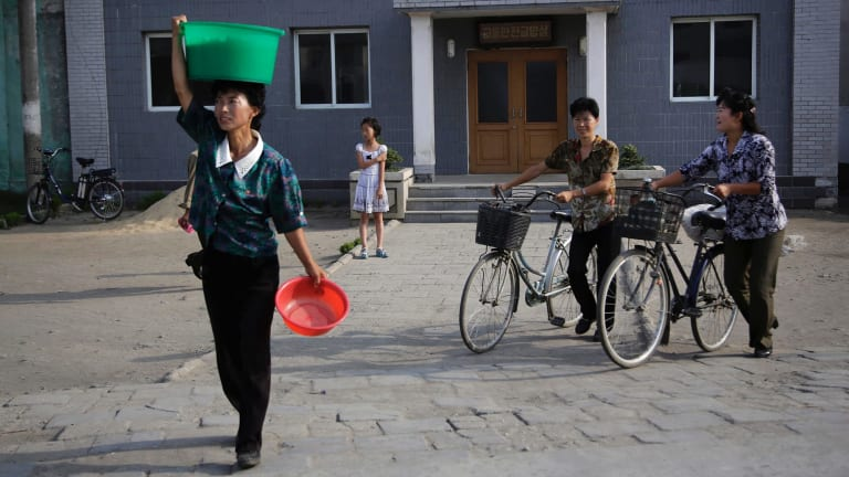 North Korean women make their way across a road in North Korea's second-largest city, Hamhung, on Thursday.
