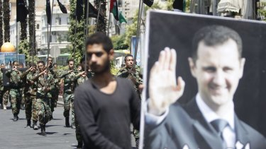 Regime loyalists carry flags as one of them holds a picture depicting Syrian President Bashar al-Assad during a rally marking Jerusalem Day in Damascus on July 10.