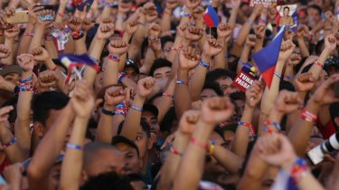 Supporters of Mr Duterte raise their clenched fists during his final campaign rally in Manila.