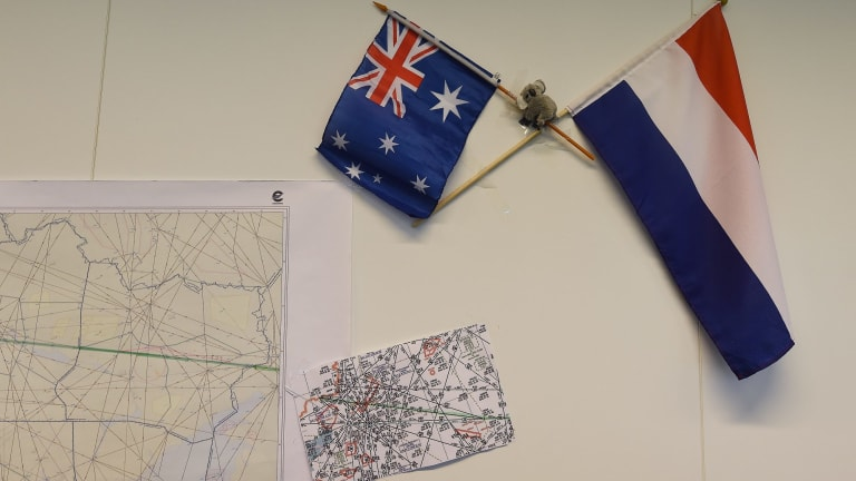Australian and Dutch flags on the wall next to maps indicating the flight path of MH17 in the National Police of the Netherlands criminal investigation building in Driebergen.