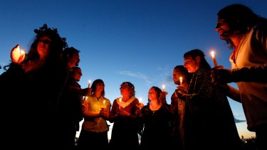 Pagans with lit candles gather at Observatory Hill to wait for Winter Solstice in June 2014.